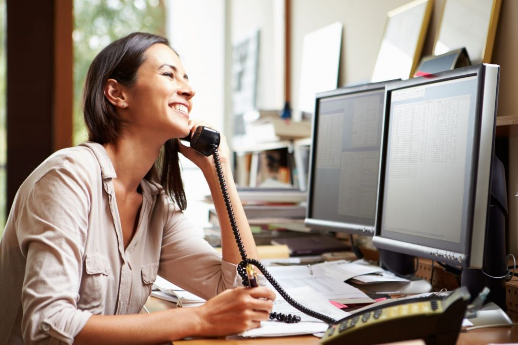 smiling woman at desk computer on voip phone
