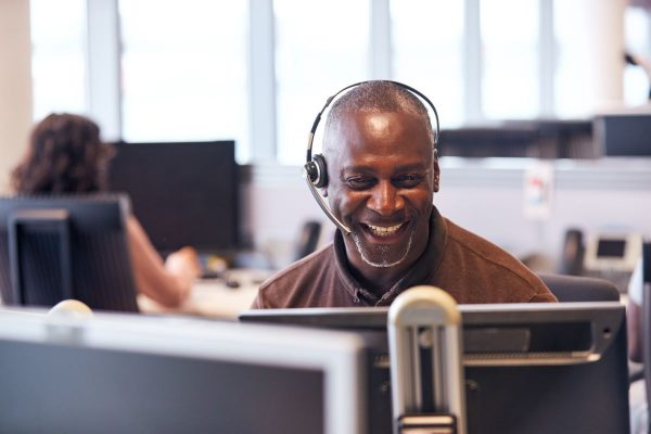 smiling man in office with phone headset
