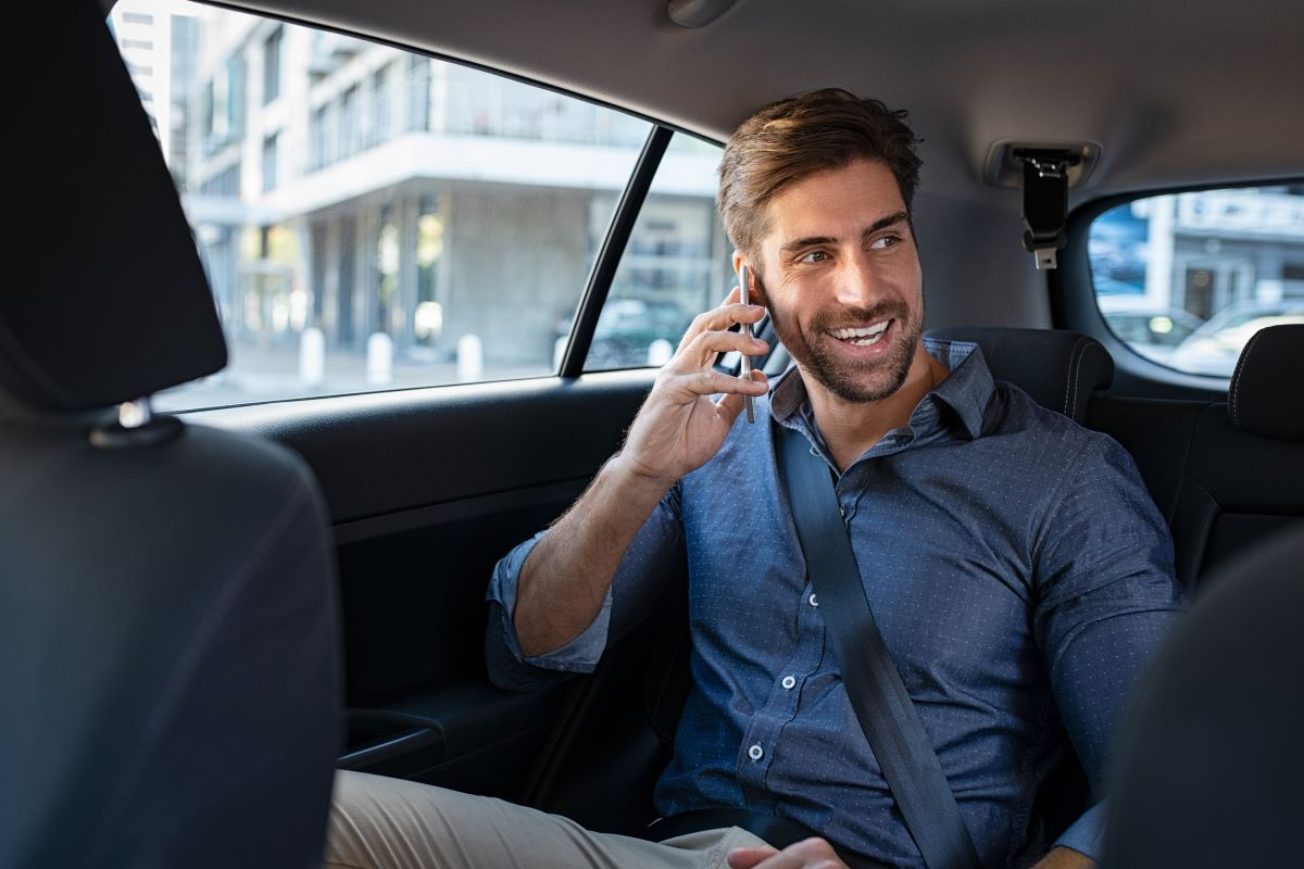 young professional man smiling while talking on cell phone in back seat of a taxi