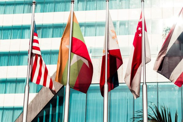 5 international flags in front of the windows of an office building