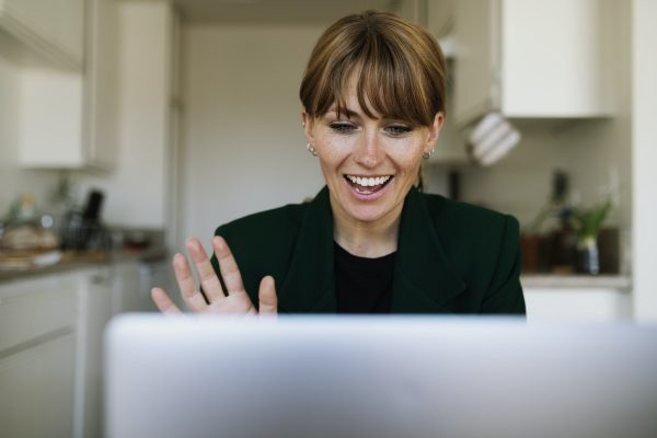 Professional woman in home smioling and waving to conference call on laptop